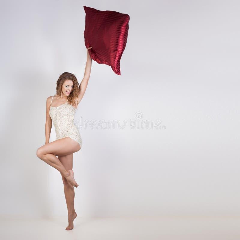 Довольно ядреная атлетическая жизнерадостная девушка в яркой пижам kravivoy поет и радуется после спать, играя с подушкой стоковое изображение