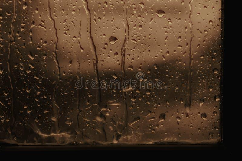Дождевая капля предпосылки на коричневом цвете стекла окна или тоне sepia стоковые фотографии rf