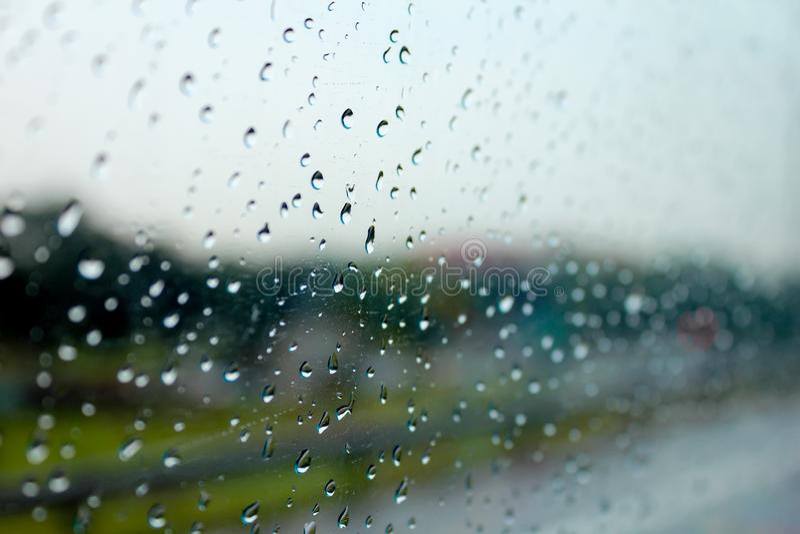 Дождевые капли на окне показывают погоду в сезоне дождей стоковые фотографии rf
