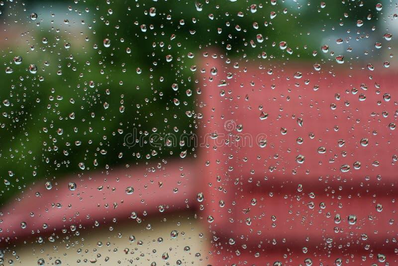 дождевые капли на стекле окна с деревьями и красной крыше как предпосылка стоковые фотографии rf