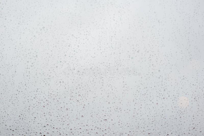 Дождевые капли на стекле окна с облачным небом как предпосылка стоковое изображение
