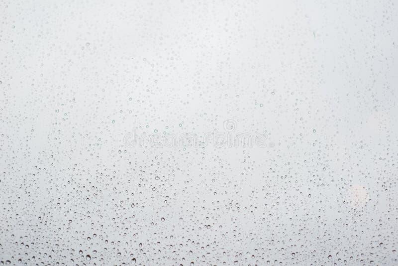 Дождевые капли на стекле окна с облачным небом как предпосылка стоковое изображение rf