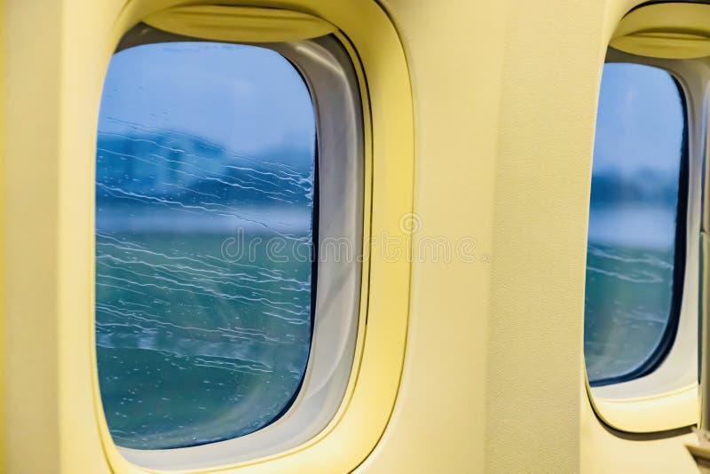 Дождь, который течет за окном самолета во время работы на ВПП стоковые фотографии rf