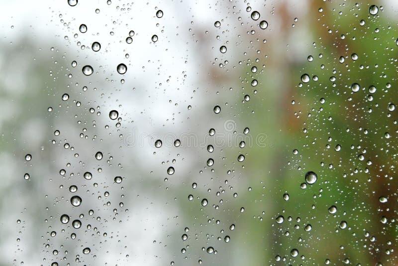 Дождь падает на окно автомобиля с тяжелым дождливым днем с драматической погодой стоковые фото