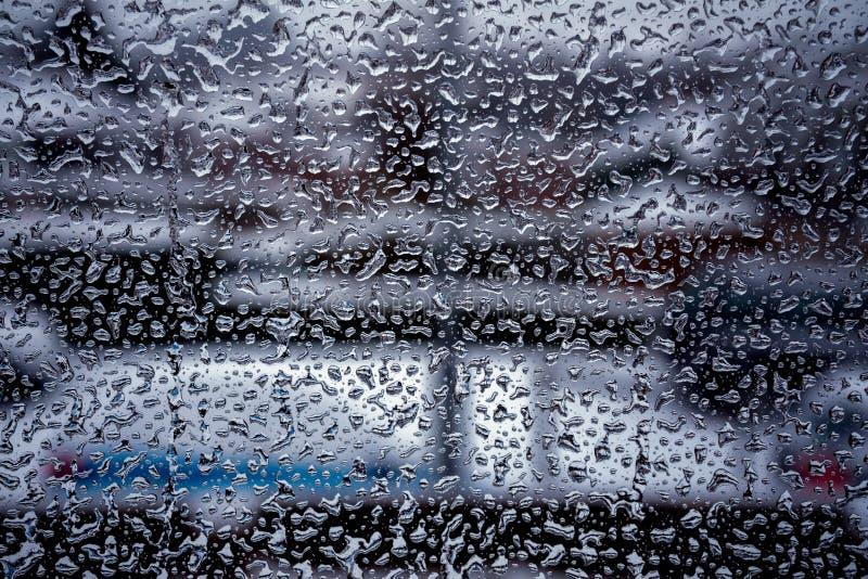 Дождь падает на поверхность стекла окна с пасмурной предпосылкой стоковое фото