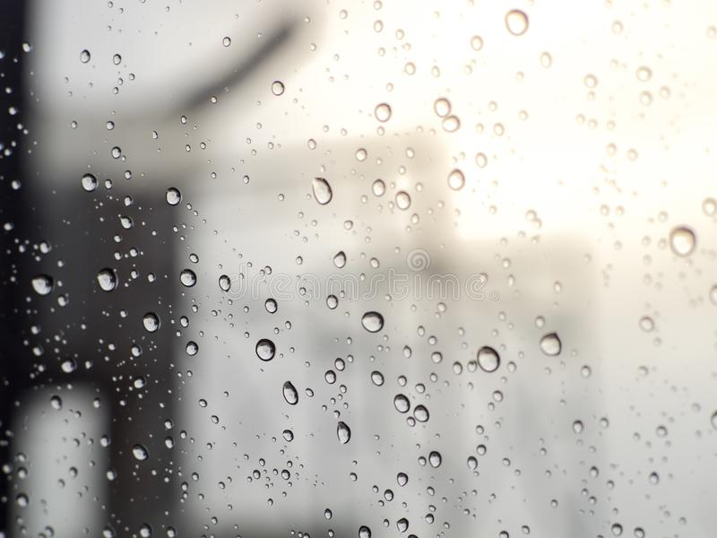 Дождь падает на стекло окна, картину дождевых капель изолированных на поверхности стекел стоковое фото