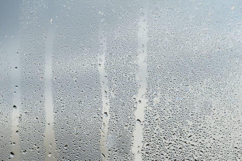 Дождевые капли и бега воды на стеклянной специализированной части окна стоковые изображения rf