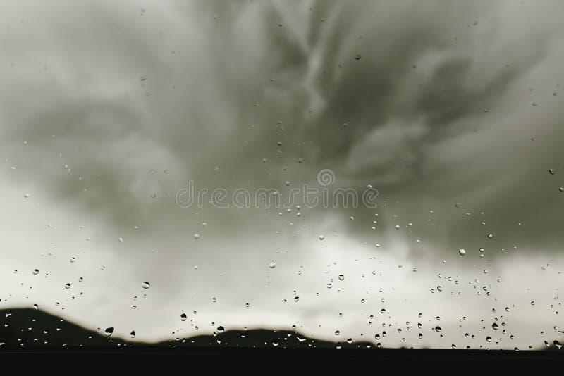 Дождевые капли на стекле окна на предпосылке серых облаков, ненастной мы стоковая фотография rf