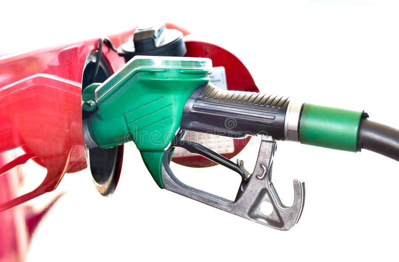 Дозаправлять красный автомобиль на бензоколонке стоковая фотография