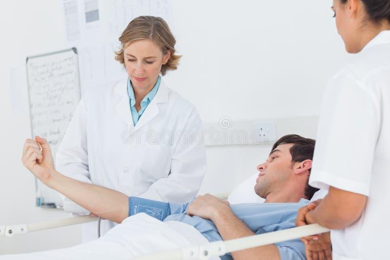 Доктора измеряя кровяное давление мужского пациента стоковое изображение rf