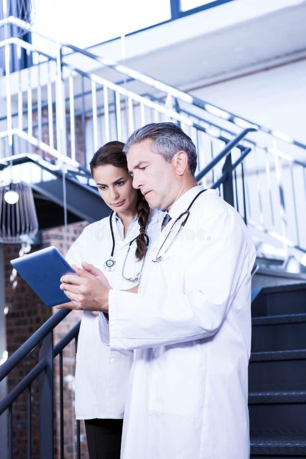 Доктора используя цифровую таблетку на лестнице стоковые изображения