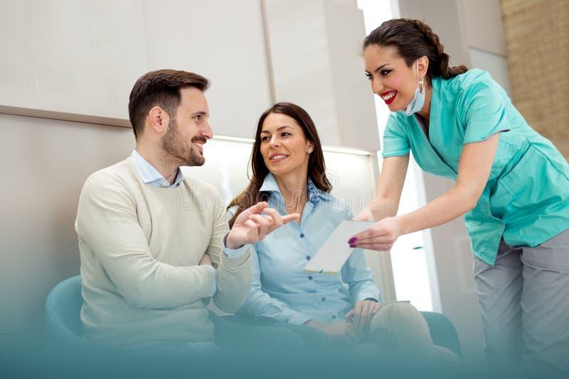 Доктора и пациенты говоря в зале ожидания больницы стоковое изображение