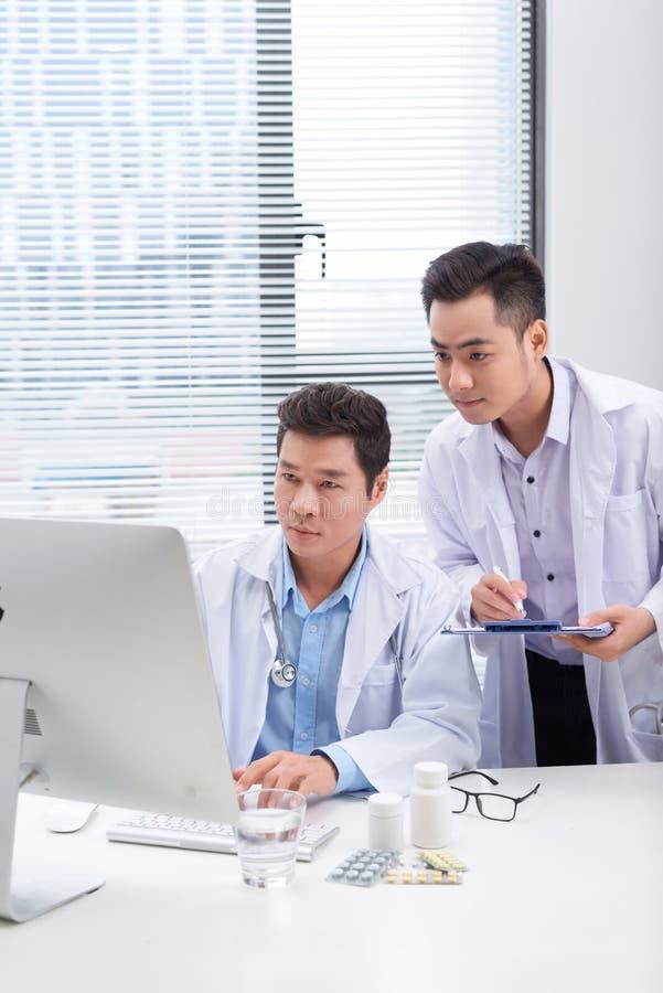 2 доктора обсуждая медицинские истории пациента стоковые фотографии rf