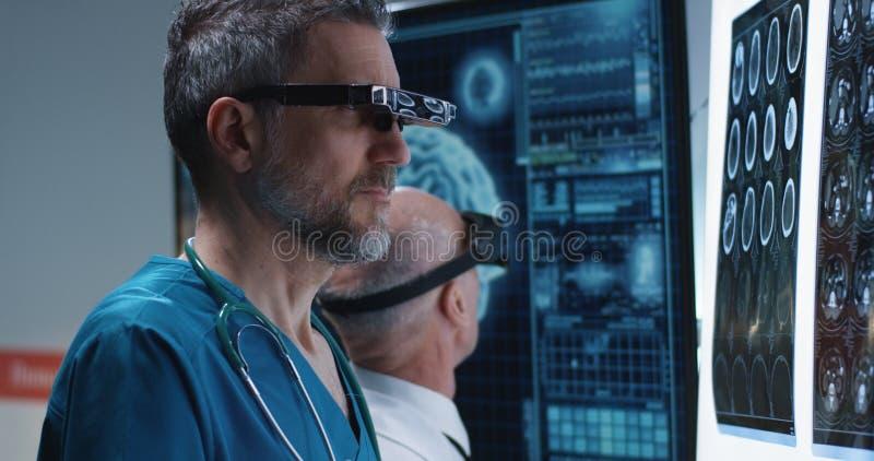 Доктора рассматривая сканирование мозга со шлемофоном VR стоковые фотографии rf