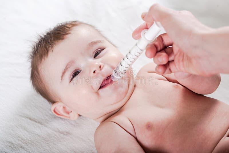 Доктор дает некоторую медицину к маленькому младенцу стоковые изображения rf