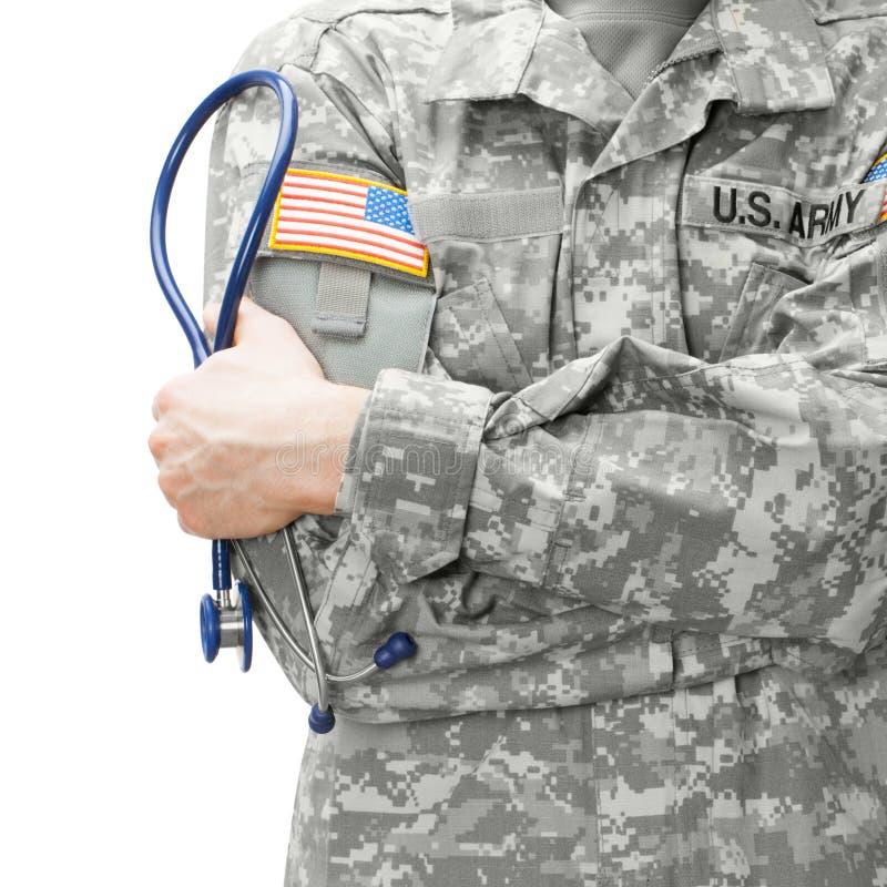 Доктор армии США держа стетоскоп рядом с его плечом - съемку студии стоковое фото