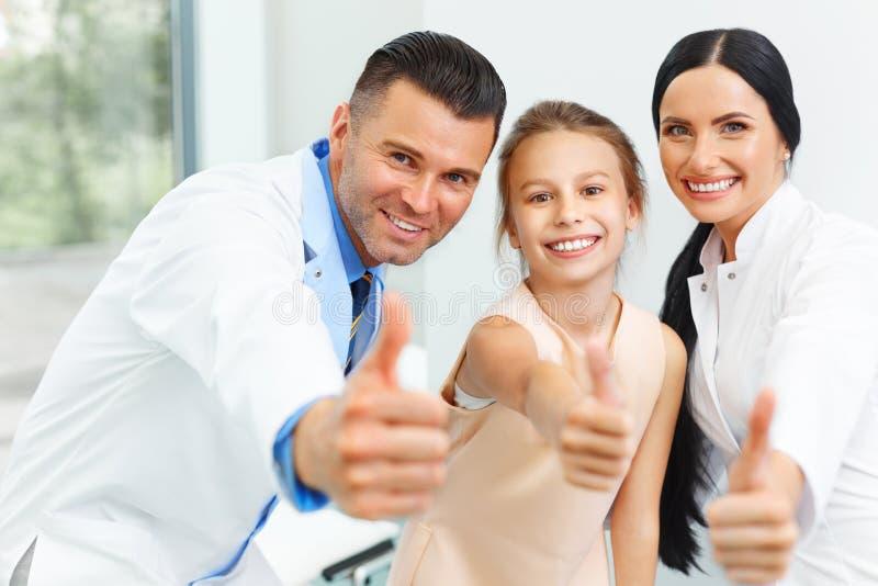 Доктор, ассистент и маленькая девочка дантиста совсем усмехаясь на камере стоковое фото