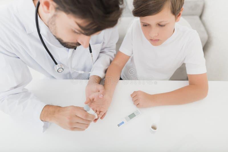Доктор берет пробу крови от мальчика для того чтобы проверить его для сахара Мальчик терпеливо терпит процедуру стоковое изображение