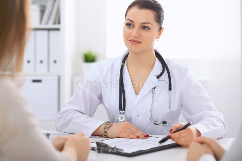 Доктор брюнет женский говоря к пациенту в офисе больницы Врач говорит о результатах медицинских обследований для стоковая фотография rf
