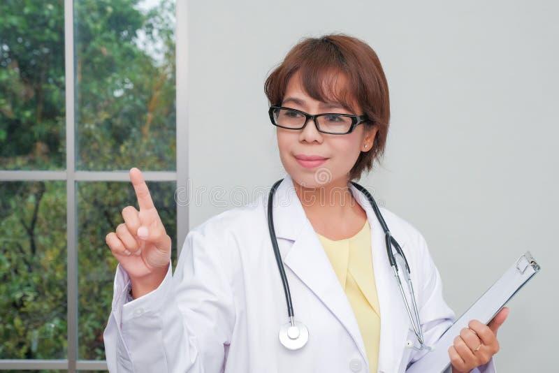 Доктор брюнет женский стоя с доской сзажимом для бумаги около окна стоковые фото
