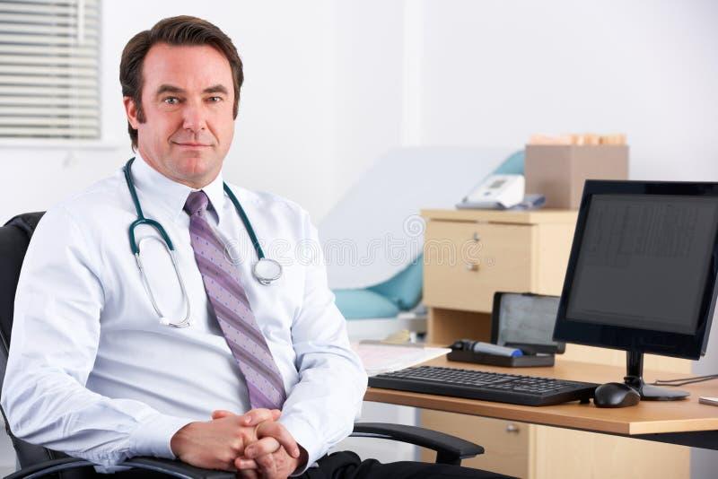 Доктор Великобритании ся на камере сидя на его столе стоковое изображение