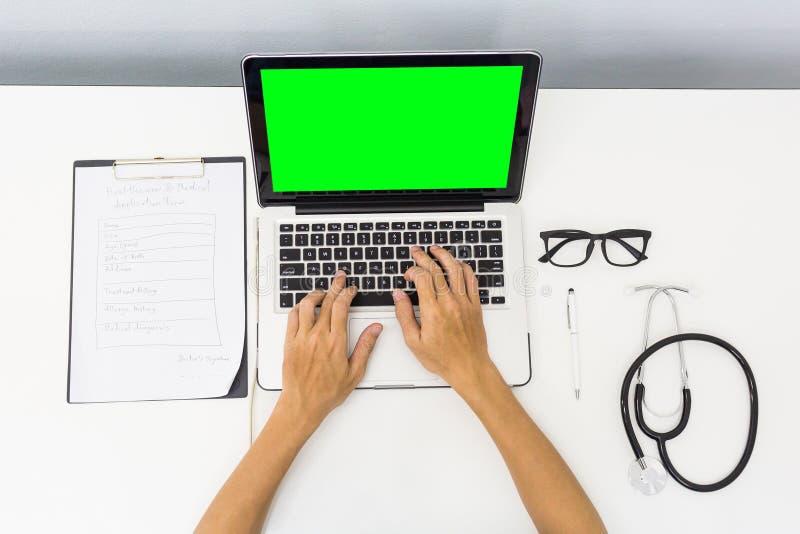 Доктор взгляд сверху работая крепко на столе с зеленым eq компьтер-книжки экрана стоковая фотография