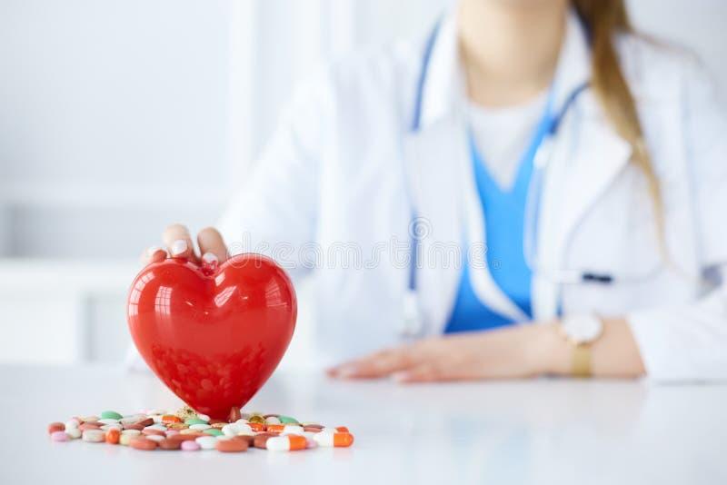 Доктор в белом пальто со стетоскопом держа таблетки и пластиковое сердце на белизне стоковое фото rf