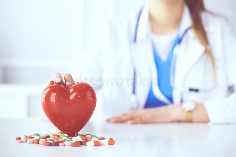 Доктор в белом пальто со стетоскопом держа таблетки и пластиковое сердце изолированными на белизне стоковое изображение