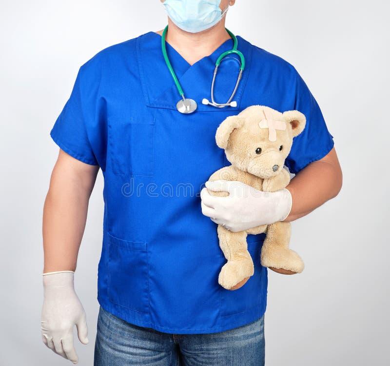доктор в голубой форме и белых перчатках латекса держа коричневую плюшевый мишку стоковое изображение rf