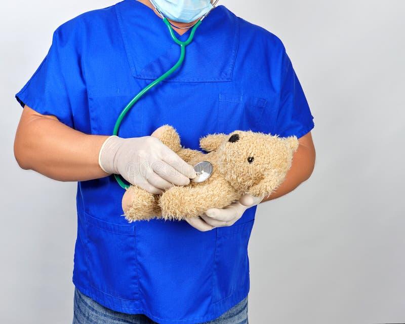 доктор в голубой форме и белых перчатках латекса держа коричневую плюшевый мишку стоковая фотография rf