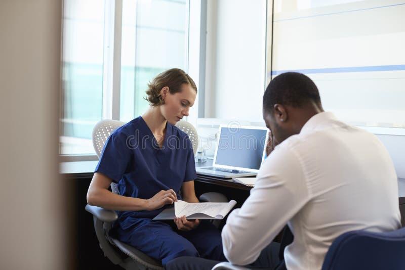 Доктор в консультации c подавленным мужским пациентом стоковое фото rf