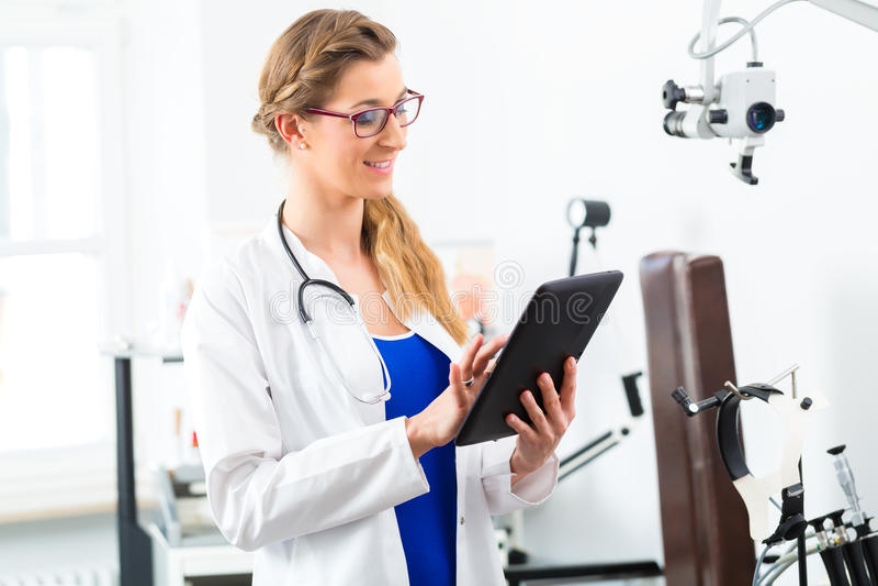 Доктор в клинике читая цифровой файл на планшете стоковое фото rf