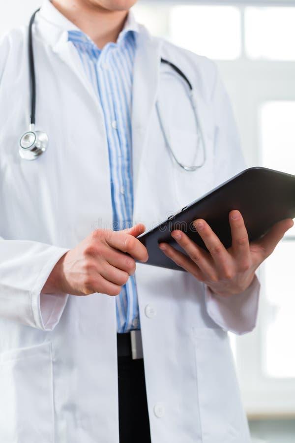 Доктор в клинике читая цифровой файл на планшете стоковая фотография rf