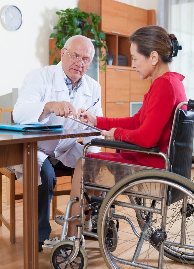 Доктор говоря к женщине в кресло-коляске стоковая фотография
