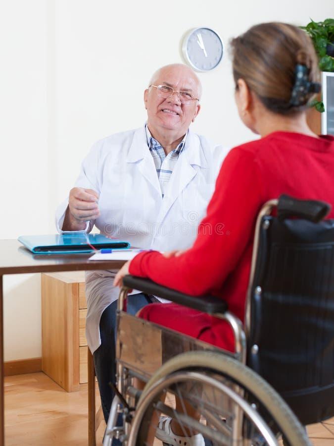 Доктор говоря к женщине в кресло-коляске стоковое изображение rf