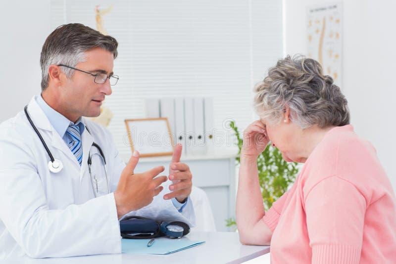 Доктор говоря к tensed пациенту стоковые фотографии rf