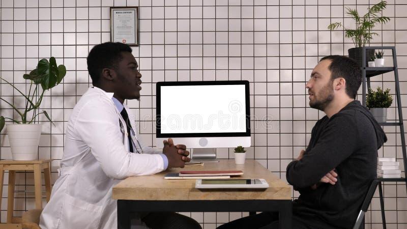 Доктор говоря с его мужским пациентом Белый дисплей стоковые фотографии rf
