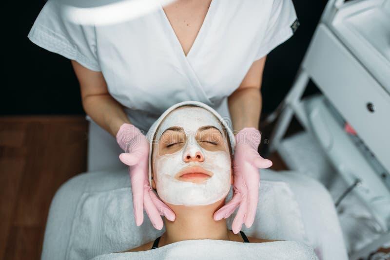 Доктор делает лицевой щиток гермошлема с сливк, женским пациентом стоковое фото