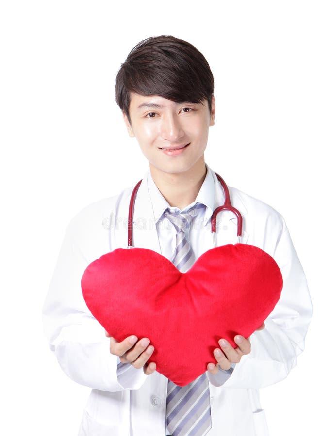 Доктор держа красную подушку сердца влюбленности стоковые фото