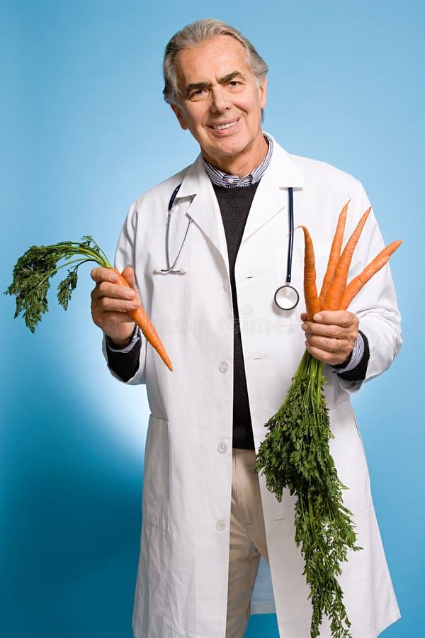 Доктор держа морковей стоковые фотографии rf