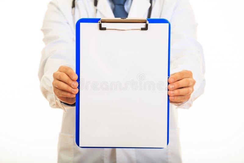 Доктор держа доску сзажимом для бумаги на белой предпосылке стоковая фотография rf