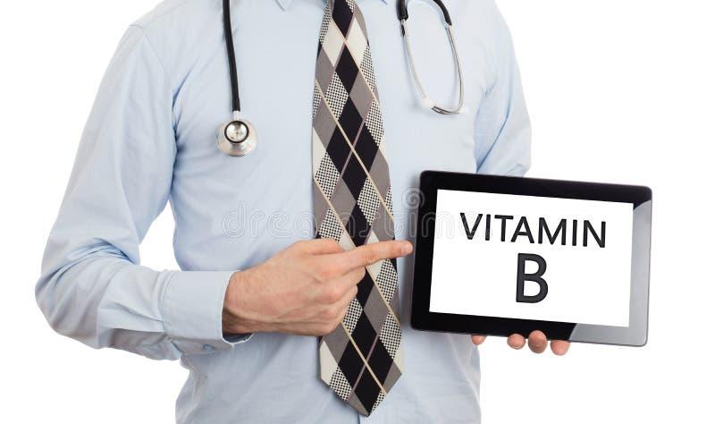 Доктор держа таблетку - Витамин B стоковое фото