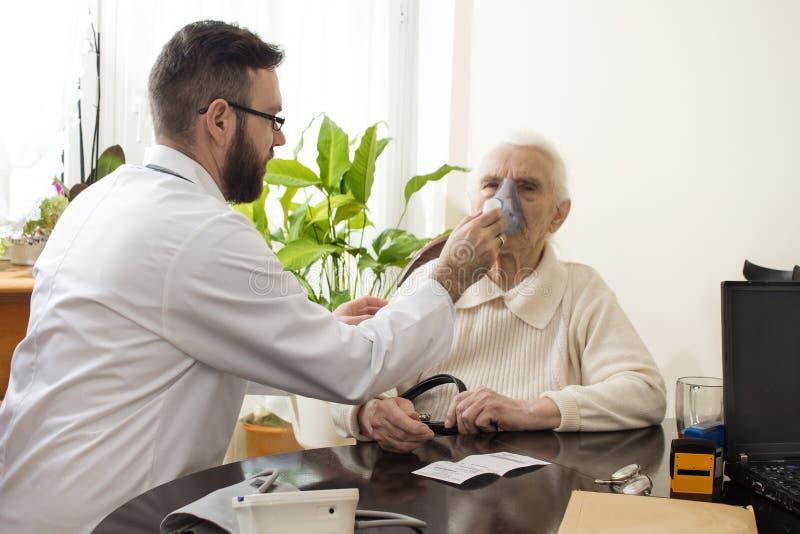 Доктор держит ингалятор сторона старухи стоковые фото