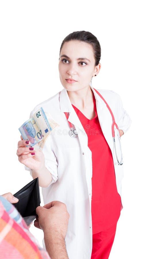 Доктор женщины принимая взятку от мужского пациента стоковые фото