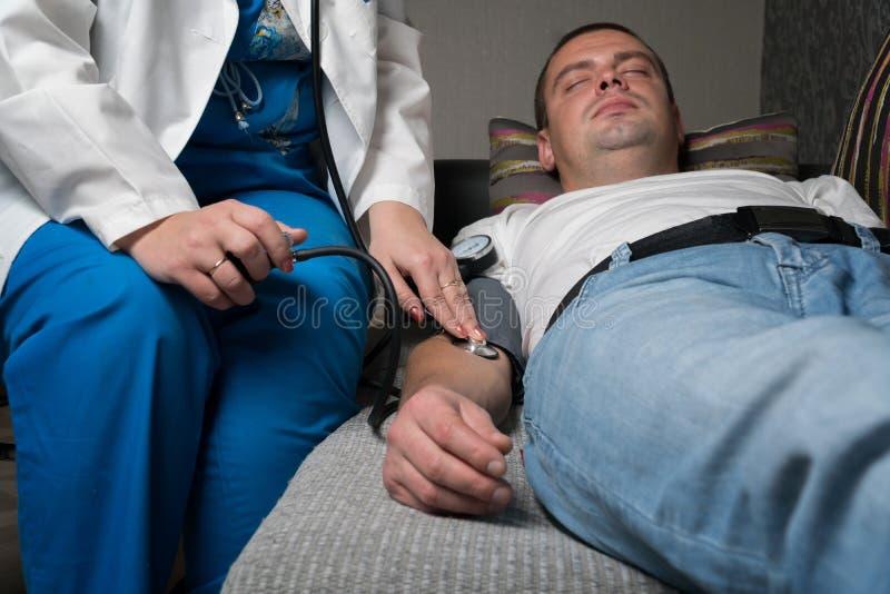 Доктор измеряет давление пациента дома стоковая фотография rf