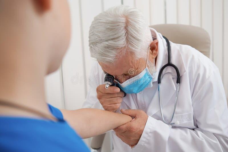 Доктор используя инструмент для рассматривать руку пациента стоковые фотографии rf