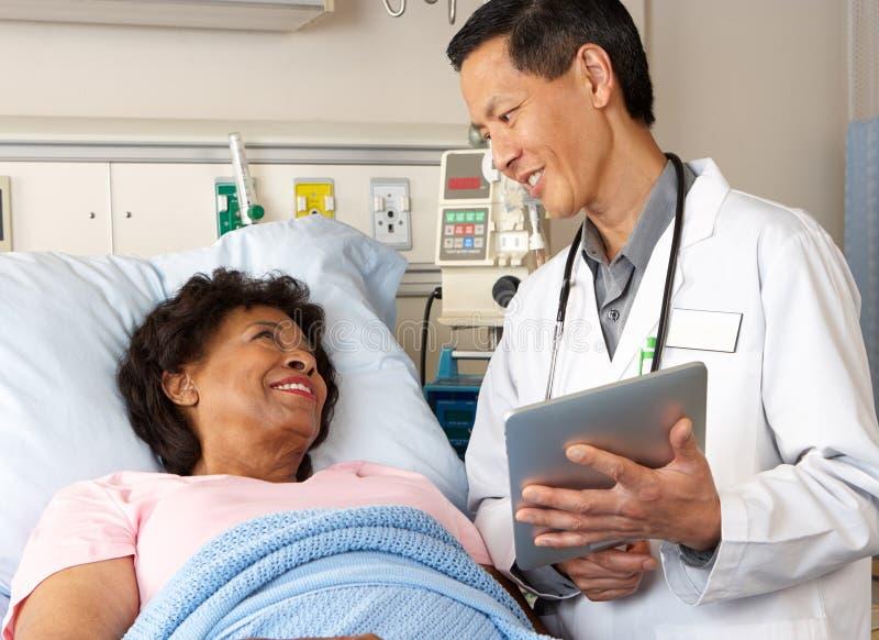 Доктор Используя Цифров Таблетка Talking с старшим пациентом стоковое фото rf