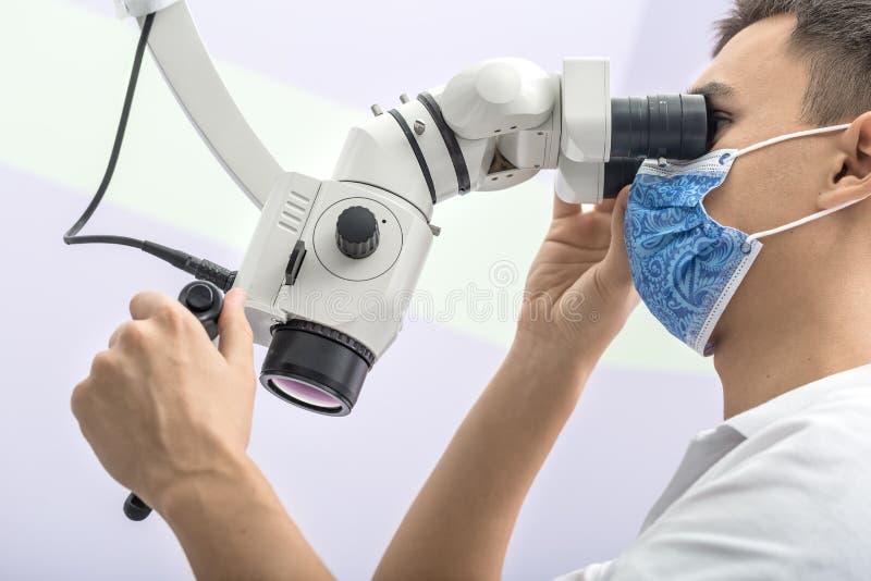 Доктор используя зубоврачебный микроскоп стоковая фотография