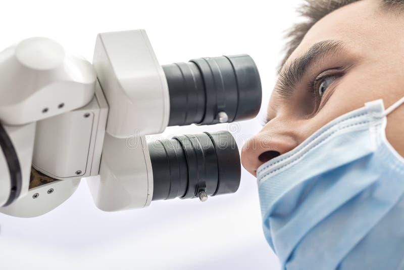 Доктор используя зубоврачебный микроскоп стоковое фото rf