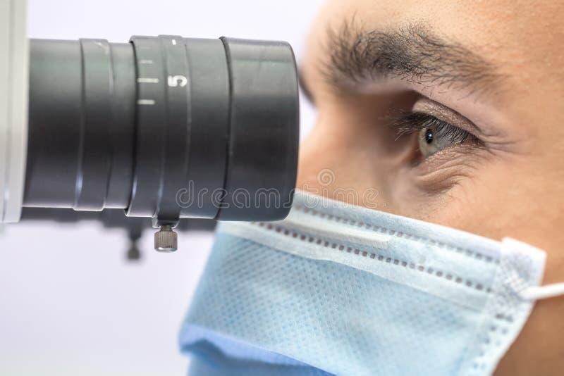 Доктор используя зубоврачебный микроскоп стоковые изображения
